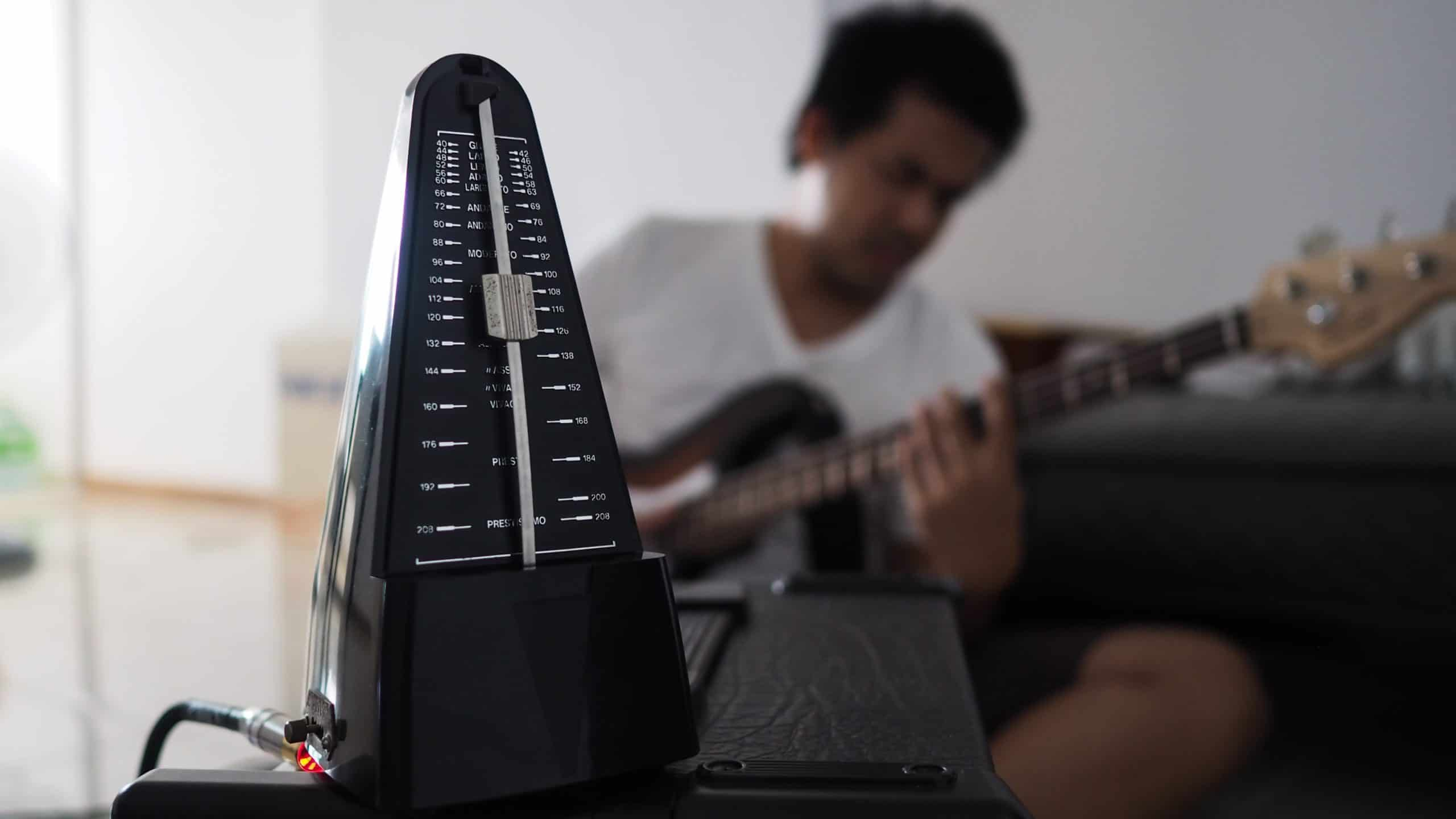 Black metronome is used by musician to help keep a steady tempo as he play
